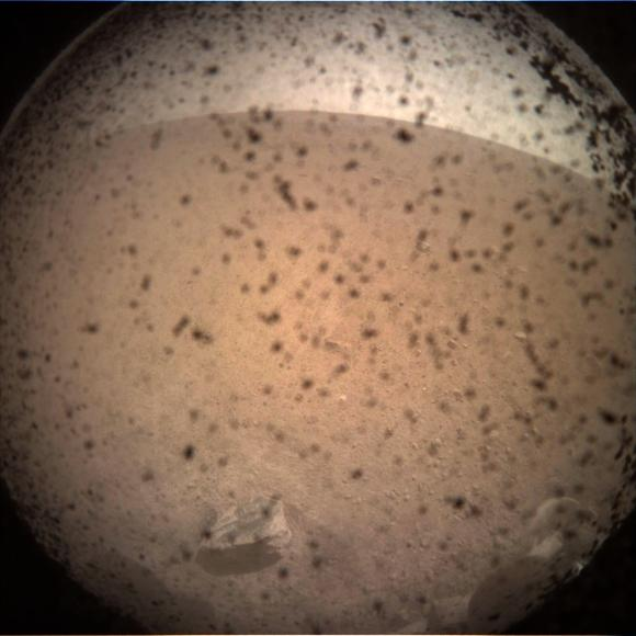 Prima fotografie trimisă de Insight de pe Marte, de o cameră instalată sub modul, la câteva momente după amartizare. Punctele negre reprezintă praful așezat pe lentila de protecție. Foto: NASA